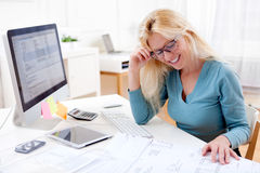 Blonde architect watching blueprint at the office Stock Photo