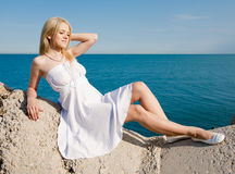 Blonde with arm raised on background of sea Stock Photography