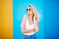 Blonde Art der recht jungen Frau mit gegen der bunten Wand Lizenzfreie Stockfotos