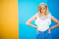 Blonde Art der recht jungen Frau mit gegen der bunten Wand Lizenzfreies Stockfoto