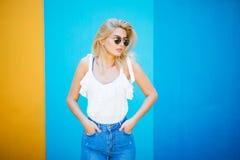 Blonde Art der recht jungen Frau mit gegen der bunten Wand Stockbilder
