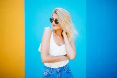Blonde Art der recht jungen Frau mit gegen der bunten Wand Stockfoto