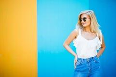 Blonde Art der recht jungen Frau mit gegen der bunten Wand Stockfotos
