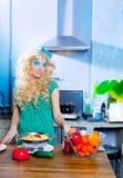 Blonde Art und Weise lustig auf Küche mit Teigwaren und Stockfoto