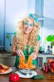 Blonde Art und Weise lustig auf Küche mit Teigwaren und Stockfotografie