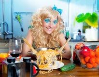 Blonde Art und Weise lustig auf Küche mit Teigwaren und Stockbilder