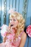 Blonde Art und Weiseprinzessinfrau, die Schokolade isst Lizenzfreie Stockfotos