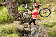 Blonde athlete carrying her mountain bike over stream Stock Photos