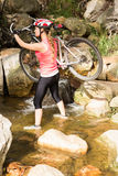 Blonde athlete carrying her mountain bike over stream Stock Images