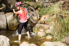 Blonde athlete carrying her mountain bike over stream Royalty Free Stock Photos