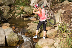 Blonde athlete carrying her mountain bike over stream Stock Image