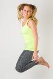 Blonde athletische Frau, die in die Luft springt Stockbild