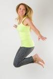 Blonde athletische Frau, die in die Luft springt Lizenzfreie Stockfotografie