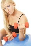 Blonde atractivo con pesas de gimnasia Imagen de archivo libre de regalías
