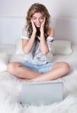 Blonde atractivo de la chica joven con la computadora portátil Imagen de archivo libre de regalías