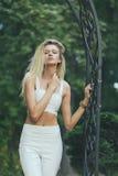 Blonde atractivo de la muchacha con el pelo largo, en un fondo verde Foto de archivo