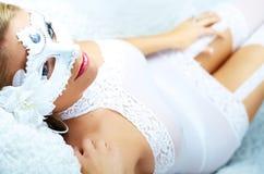 Blonde atractivo de la muchacha en la ropa interior y la máscara blancas Foto de archivo