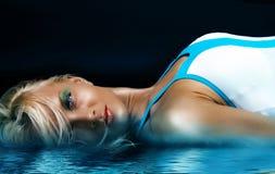 Blonde atractivo en agua azul Foto de archivo