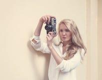Blonde atractivo hermoso con el pelo largo con la cámara del vintage a disposición, caliente, tonning Imagen de archivo libre de regalías