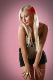 Blonde atractivo hermoso con la flor roja en pelo Imagen de archivo