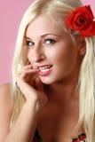 Blonde atractivo hermoso con la flor roja en pelo Imagen de archivo libre de regalías