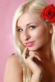 Blonde atractivo hermoso con la flor roja en pelo Fotos de archivo libres de regalías