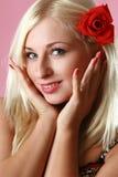 Blonde atractivo hermoso con la flor roja en pelo Imágenes de archivo libres de regalías