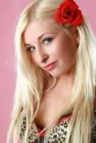 Blonde atractivo hermoso con la flor roja en pelo Fotos de archivo