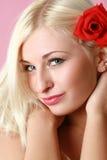 Blonde atractivo hermoso con la flor roja en pelo Imagenes de archivo