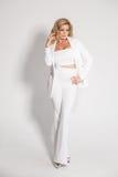 Blonde atractivo hermoso en un traje blanco que presenta en el fondo blanco Imagen de archivo libre de regalías