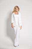 Blonde atractivo hermoso en un traje blanco que presenta en el fondo blanco Foto de archivo