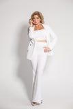 Blonde atractivo hermoso en un traje blanco que presenta en el fondo blanco Imagen de archivo