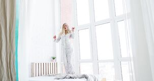 Blonde atractivo joven en los pijamas que bailan en cama en su dormitorio almacen de metraje de vídeo