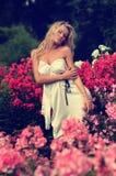 Blonde atractivo que presenta las flores de Amonst Imágenes de archivo libres de regalías