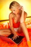 Blonde atractivo que usa el ordenador portátil Foto de archivo