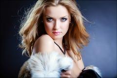 Blonde atractivo sensual en un abrigo de pieles en un fondo azul, clo de la muchacha Fotos de archivo libres de regalías