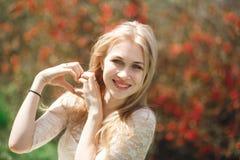 Blonde attirante dans le jardin de floraison de ressort Main du ` s de femmes avec une forme de coeur au jardin de fleur Images libres de droits