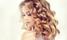 Blonde attirante de femme avec les cheveux de longueur, denses et bouclés moyens image libre de droits