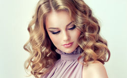 Blonde attirante de femme avec les cheveux de longueur, denses et bouclés moyens photos stock
