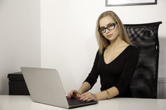 Blonde attractive businesswoman in office. Business concept - portrait of a beauty young adult attractive pretty blonde businesswoman in office Stock Images