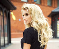 Blonde attractive girl. Blonde beautiful woman with long curly hair stock photography