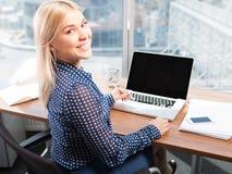 Blonde attraktive Frau, die Laptop verwendet Stockbild