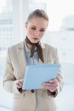 Blonde attraktive Geschäftsfrau, die Tablette hält Lizenzfreie Stockfotografie