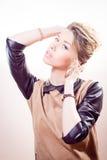 Blonde attraktive junge Frau des gesammelten blonden Haares im braunen Kleid mit ledernen Ärmeln und dem Kragen, die Kamera betrac Lizenzfreie Stockfotografie