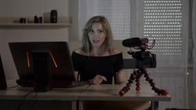 Blonde attraktive weibliche Videobloggerschmierfilmbildung selbst mit einer Kamera an unterrichtendem Publikum des Büros, wie man stock video footage
