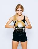 Blonde Aufstellung als Mädchen des amerikanischen Fußballs auf weißem Hintergrund Schöne junge Frau, die schwarze Ausstattung mit Stockfoto