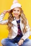 Blonde Aufstellung des kleinen Mädchens im Studio auf gelbem Hintergrund Lizenzfreie Stockfotos