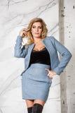 Blonde Aufstellung des schönen sexy Geschäfts auf einem Marmorhintergrund Lizenzfreie Stockbilder