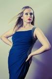 Blonde Aufstellung in einem blauen Kleid Stockbild