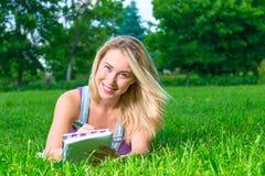 Blonde Aufstellung in einem Park, der auf dem Rasen liegt Stockfotos